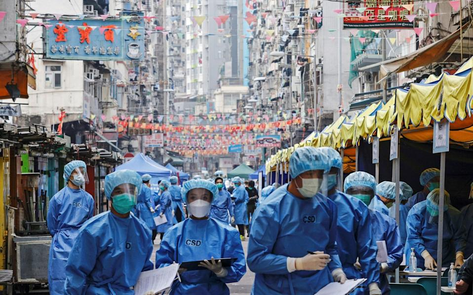 Health workers are seen in protective gear inside a locked down portion of the Jordan residential area to contain a new outbreak of the coronavirus in Hong Kong - EUTERS/Tyrone Siu