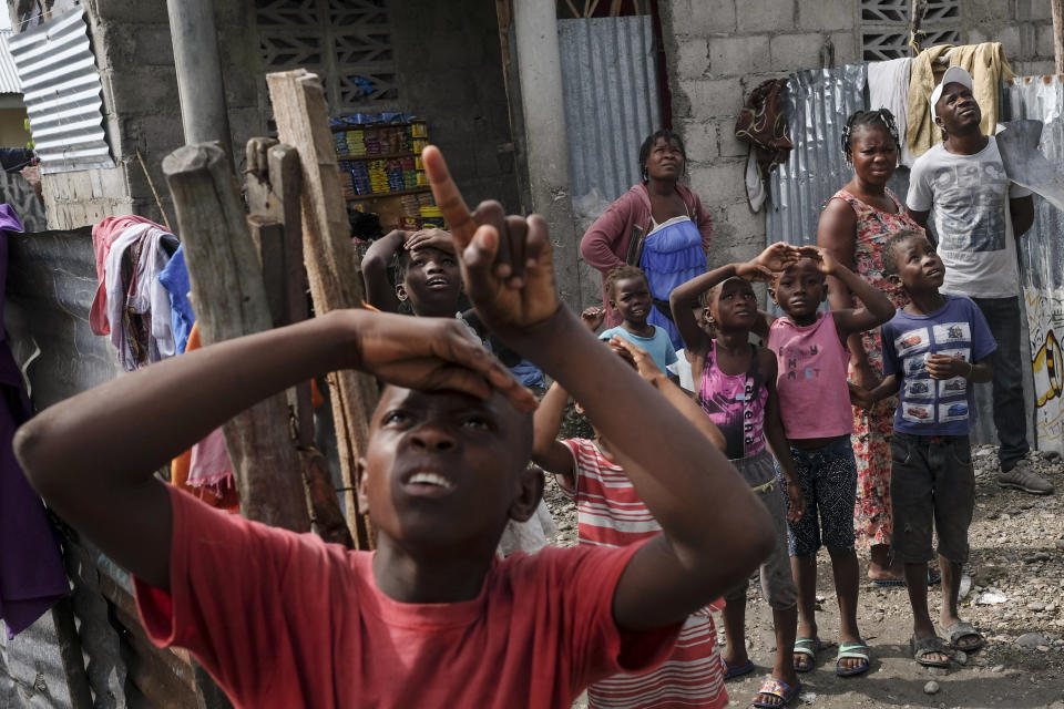 A boy points at an approaching helicopter bringing aid for earthquake survivors in a neighborhood near the airport in Les Cayes, Haiti, Thursday, Aug. 19, 2021. (AP Photo/Matias Delacroix)