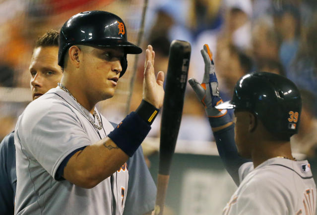 Detroit Tigers' Miguel Cabrera, front left, is congratulated by teammate Ramon Santiago, right, after scoring in the fifth inning of a baseball game at Kauffman Stadium in Kansas City, Mo., Friday, Sept. 6, 2013. (AP Photo/Orlin Wagner)