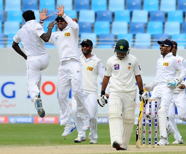 Sri Lankan bowler Shaminda Eranga (L) with teammates celebrates the dismissal of Pakistan batsman Asad Shafiq (C) during the fourth day of the second cricket Test match between Pakistan and Sri Lanka at the Dubai International Cricket Stadium in Dubai on January 11, 2014.  AFP PHOTO/Ishara S. KODIKARA