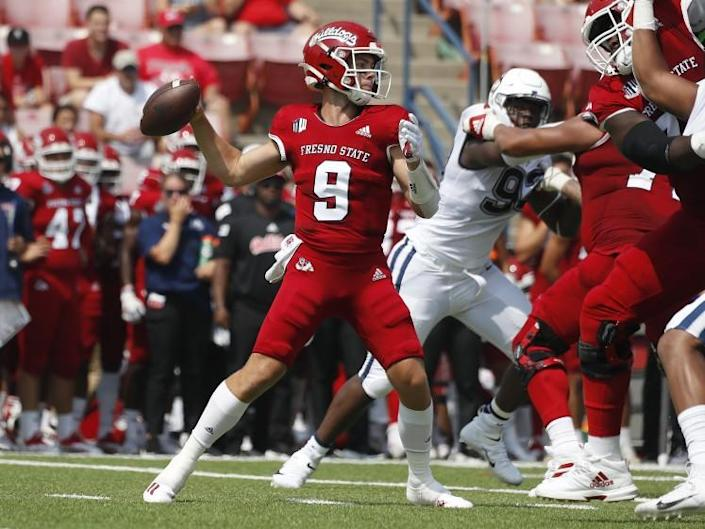 Fresno State quaterback Jake Haener throws a pass past Connecticut defenders.