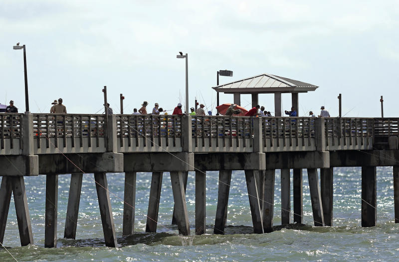 A group of people fishing at Dania Beach Pier on Saturday, August 31, 2019 at Dania Beach in Florida. As of the 11 a.m. advisory, Hurricane Dorian is a category 4 storm. (David Santiago/Miami Herald via AP)
