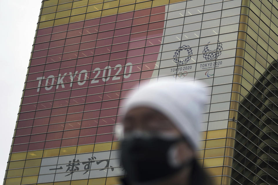 A man wearing a protective mask to help curb the spread of the coronavirus walks near a banner of the Tokyo 2020 Olympics and Paralympics Wednesday, Jan. 27, 2021, in Tokyo. (AP Photo/Eugene Hoshiko)