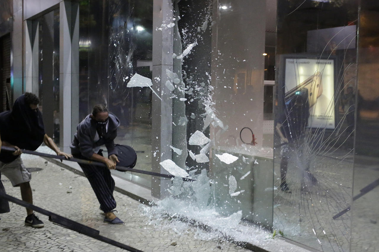 <p>Protesters shatter the glass of a bank during a demonstration against federal government proposed reforms in Rio de Janeiro, Brazil, Wednesday, March 15, 2017. People protested across the country against proposed changes to work rules and pensions. (Leo Correa/AP) </p>