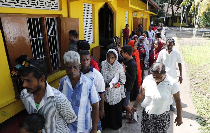 Sri Lankans queue to cast their votes at a polling station during the presidential election in Colombo, Sri Lanka, Saturday, Nov. 16, 2019. Polls opened in Sri Lanka's presidential election Saturday after weeks of campaigning that largely focused on national security and religious extremism in the backdrop of the deadly Islamic State-inspired suicide bomb attacks on Easter Sunday. (AP Photo/Eranga Jayawardena)
