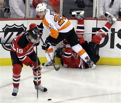New Jersey Devils' Ilya Kovalchuk, of Russia, is knocked onto his back by Philadelphia Flyers' Matt Carle (25) as Devils' Travis Zajac (19) takes control of the puck in overtime of Game 3 of a second-round NHL hockey Stanley Cup playoff series, Thursday, May 3, 2012 in Newark, N.J. The Devils won 4-3 and took a 2-1 lead in the series. (AP Photo/Julio Cortez)