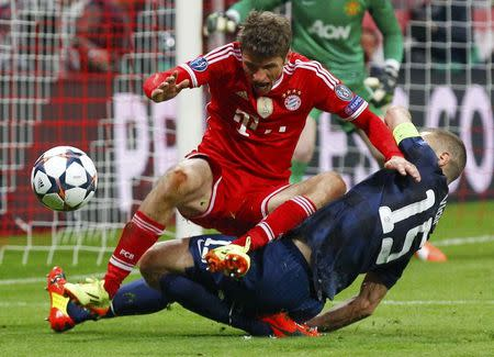 Bayern Munich's Mueller challenges Manchester United's Vidic during their Champions League quarter-final second leg soccer match in Munich