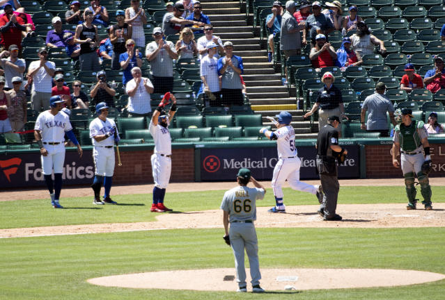Texas Rangers' Tim Federowicz (50) is congratulated by Rougned Odor, Shin-Soo Choo and Ronald Guzman (right to left) as Oakland Athletics relief pitcher Ryan Dull (66) looks on during the fifth inning iin the first baseball game of a doubleheader Saturday, June 8, 2019, in Arlington, Texas. (AP Photo/Jeffrey McWhorter)