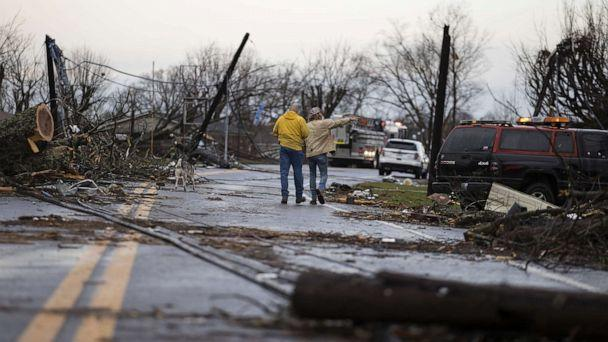 PHOTO: Residents walk through downed utility lines and trees to survey damage caused by one of several tornadoes that tore through the state overnight, March 3, 2020, in Cookeville, Tenn. (Brett Carlsen/Getty Images)