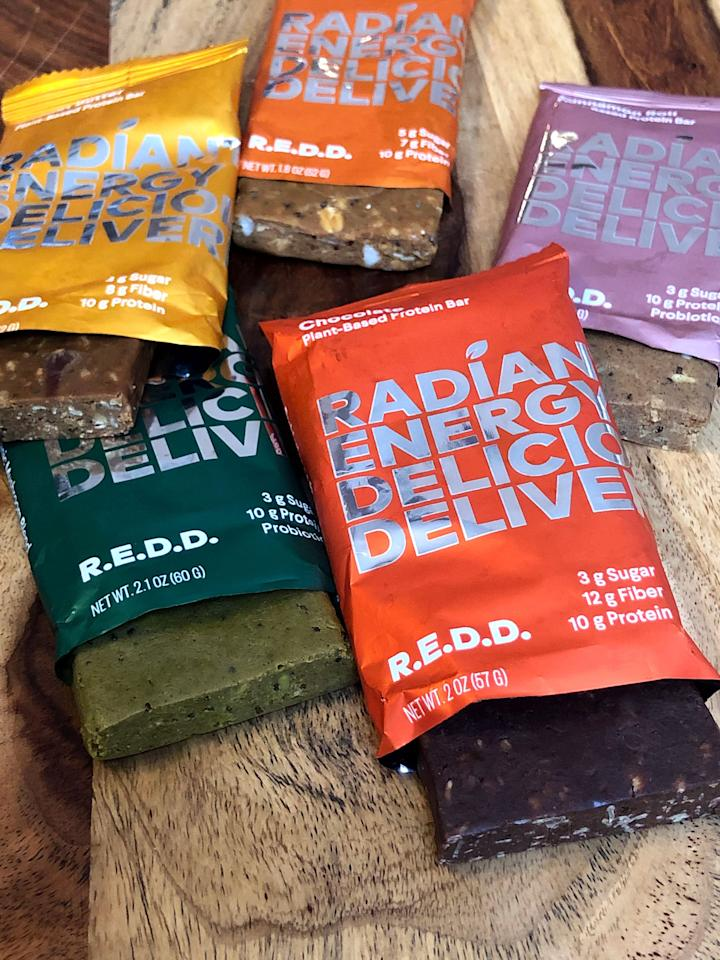 """<p>The R.E.D.D. letters in these plant-based protein bars stand for """"radiant energy deliciously delivered."""" They're made with a protein blend of pea, hemp, and pumpkin seeds and also contain dates, nuts, chia seeds, and oats. On the ingredients list is also a superfood blend including maca root powder, reishi mushroom powder, goji berries, acai powder, and turmeric. These bars also offer probiotics.</p>"""