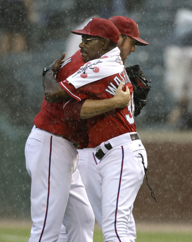 Rains falls as Texas Rangers closer Joe Nathan, left, hugs manger Ron Washington after their 7-4 win in a baseball game against the Los Angeles Angels Saturday, Sept. 28, 2013, in Arlington, Texas. (AP Photo/LM Otero)