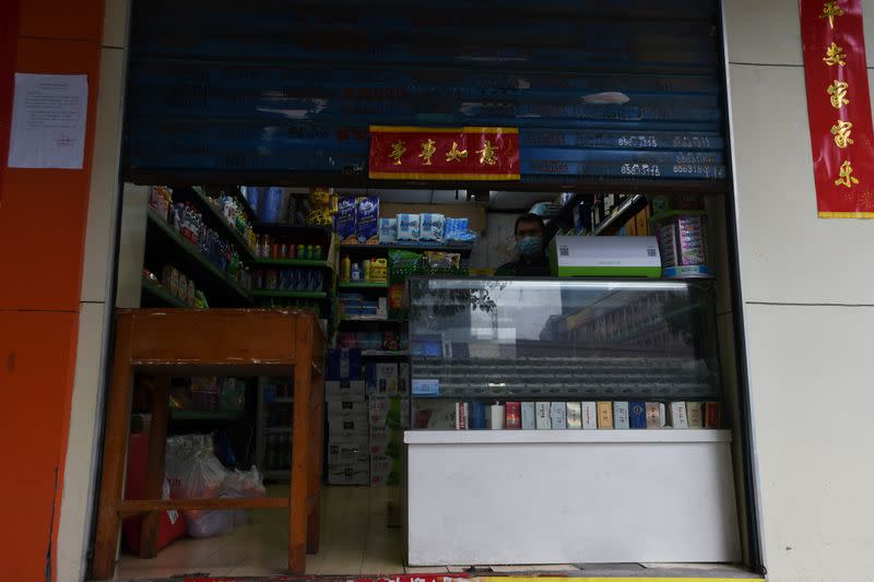 Man wearing a face mask stands inside a shop with the roller shutter half closed, in Wuhan, the epicentre of the novel coronavirus outbreak