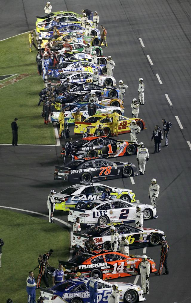 Cars line up along the front stretch before the NASCAR Sprint All-Star auto race at Charlotte Motor Speedway in Concord, N.C., Saturday, May 17, 2014. (AP Photo/Gerry Broome)