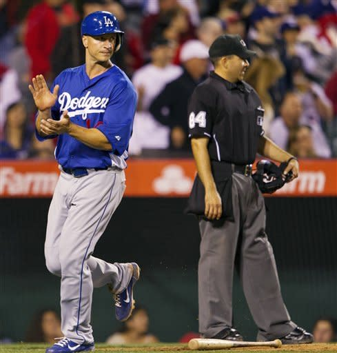 Los Angeles Dodgers' Mark Ellis scores a run after a hit by Juan Rivera against the Los Angeles Angels during the fourth inning of a spring training baseball game, Monday, April 2, 2012, in Anaheim, Calif. (AP Photo/Jeff Lewis)