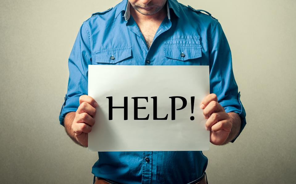 Midsection Of Depressed Mid Adult Man Holding Help Wanted Sign Against Gray Background