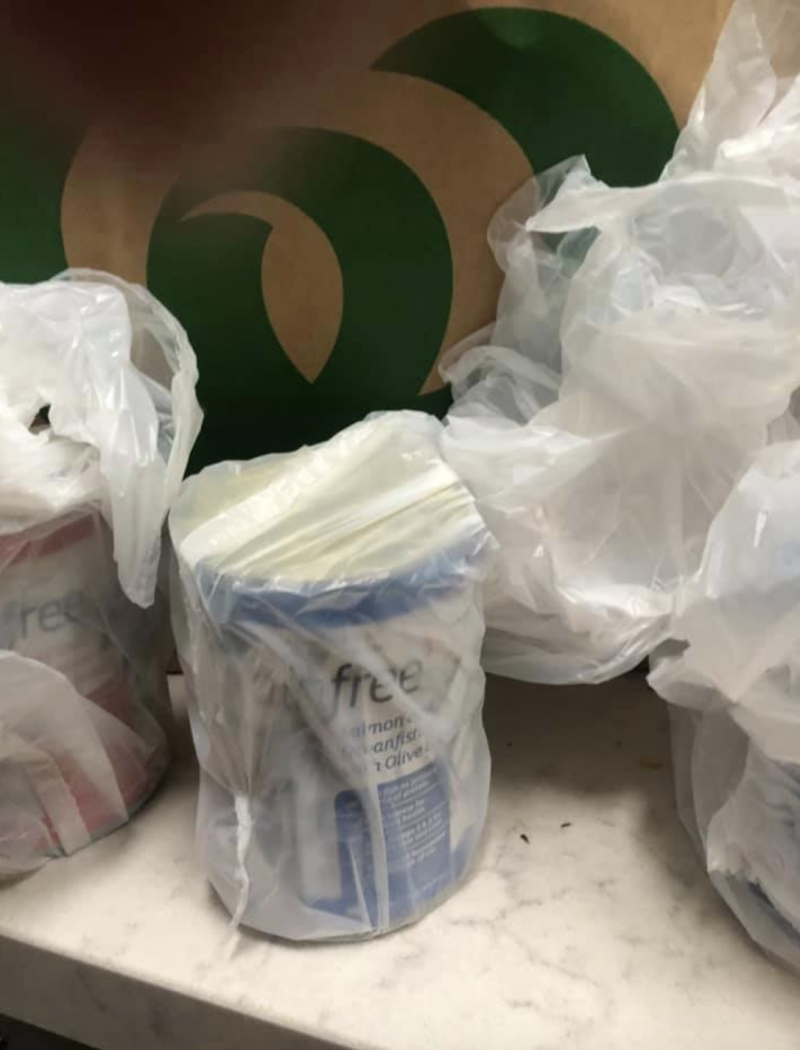 Several cans of cat food packed in separate plastic bags sit on the Woolworths shopper's kitchen bench with a paper bag in the background.