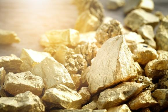 Gold nuggets on a flat surface.