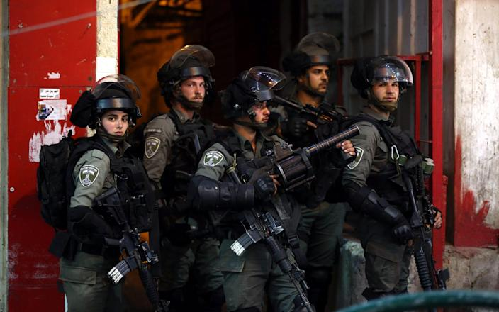 Israeli troops are seen during clashes with Palestinian protesters in the city center of the West Bank city of Hebron