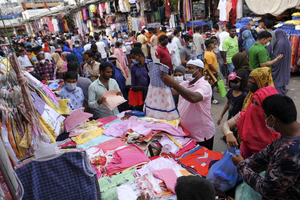 People shop at a market ahead of Eid-al Adha in Dhaka, Bangladesh, Friday, July 16, 2021. Millions of Bangladeshis are shopping and traveling during a controversial eight-day pause in the country's strict coronavirus lockdown that the government is allowing for the Islamic festival Eid-al Adha. (AP Photo/Mahmud Hossain Opu)