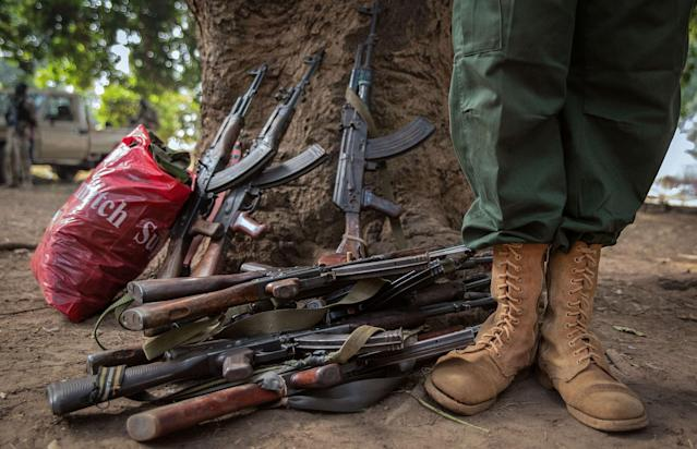<p>A former child soldier stands next to rifles during the release ceremony for child soldiers in Yambio, South Sudan on Feb. 7, 2018. (Photo: Stefanie Glinski/AFP/Getty Images) </p>