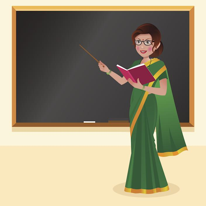 Indian teacher with reading glasses in front of blackboard with book and stick