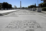 """FILE - In this Thursday, May, 16, 2019 file photo, a Fascist motto reading in Italian """"Many enemies, much honour"""", decorates the mosaic pavement on the avenue from the Olympic stadium to a fascist-era obelisk, at Rome's Foro Italico sporting ground. An extreme-right political party's violent exploitation of anger over government anti-pandemic restrictions is forcing Italy to wrestle with its fascist legacy and fueling fears that there could be a replay of last week's mobs trying to force their way toward Parliament. (AP Photo/Gregorio Borgia, File)"""