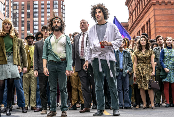 """This image released by Netflix shows, foreground from left, Caitlin Fitzgerald, Jeremy Strong and Sasha Baron Cohen in a scene from """"The Trial of the Chicago 7,"""" named one of the top 10 films of the year by The American Film Institute. (Nico Tavernise/Netflix via AP)"""