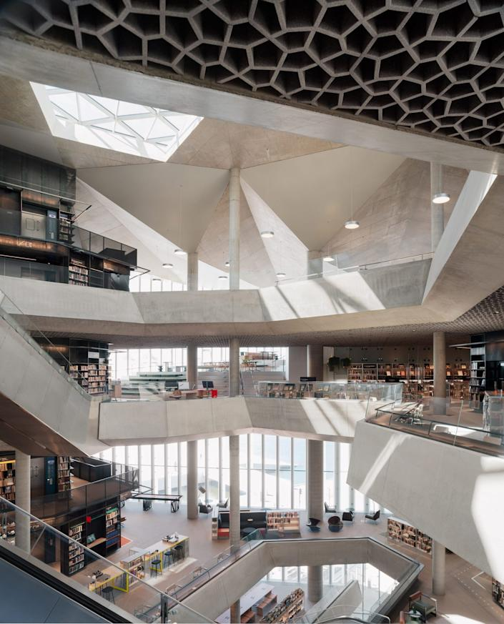 The main atrium of Oslo's new Deichman Bjørvika Public Library, complete with intricate honeycomb patterns etched into the ceiling.