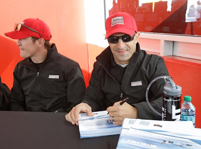 Scott Dixon, left, of New Zealand, and Tony Kanaan, of Brazil, signs autographs for fans prior to the start of the IMSA Series Rolex 24 hour auto race at Daytona International Speedway in Daytona Beach, Fla., Saturday, Jan. 25, 2014.(AP Photo/John Raoux)