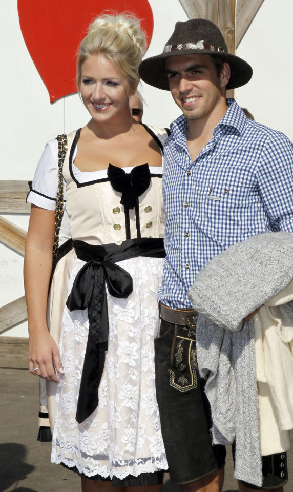 Philipp Lahm, right, of Bayern Muenchen and his wife Claudia arrive a beer tent during the 178th Oktoberfest beer festival in Munich, southern Germany, on Sunday, Oct. 2 , 2011. (AP Photo/Matthias Schrader)