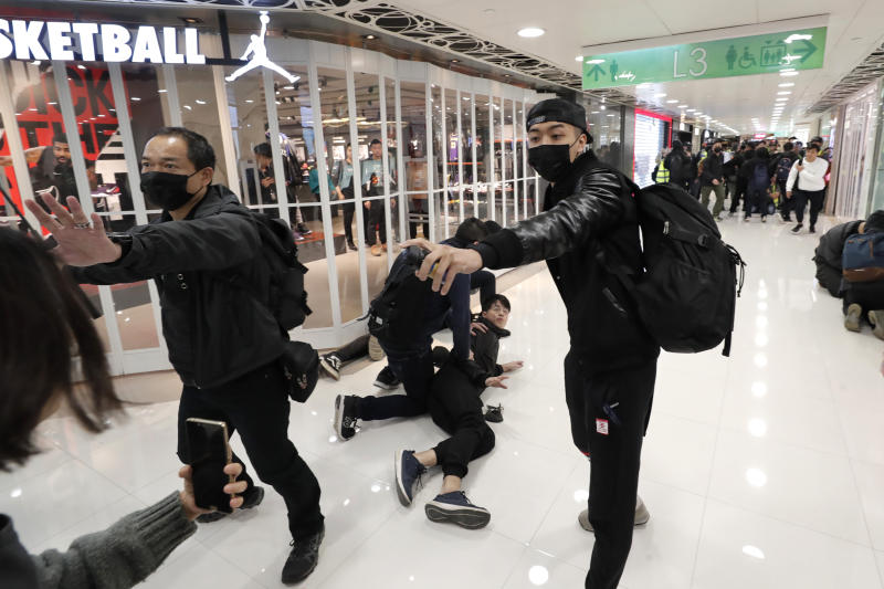 "An undercover policeman points a can of pepper spray as others detain a protester during a demonstration at a shopping mall popular with traders from mainland China near the Chinese border in Hong Kong, Saturday, Dec. 28, 2019. Protesters shouting ""Liberate Hong Kong!"" marched through a shopping mall Saturday to demand that mainland Chinese traders leave the territory in a fresh weekend of anti-government tension. (AP Photo/Lee Jin-man)"