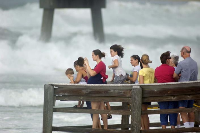A crowd gathers on the end of the boardwalk on Okaloosa Island in Fort Walton Beach, Fla., Tuesday, Aug. 28, 2012 to watch rough surf generated by Hurricane Isaac as it moves through the Gulf of Mexico with an expected landfall in Louisiana. (AP Photo/Northwest Florida Daily News, Devon Ravine)