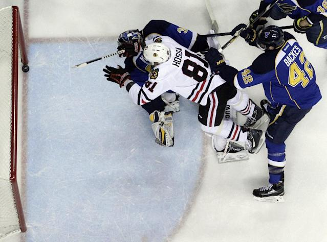 Chicago Blackhawks' Marian Hossa (81), of Slovakia, scores past St. Louis Blues goalie Ryan Miller and David Backes (42) during the first period in Game 5 of a first-round NHL hockey playoff series Friday, April 25, 2014, in St. Louis. (AP Photo/Jeff Roberson)