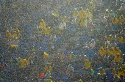 Fans sit under pouring rain during the match between Mexico and Cameroon. (AFP)