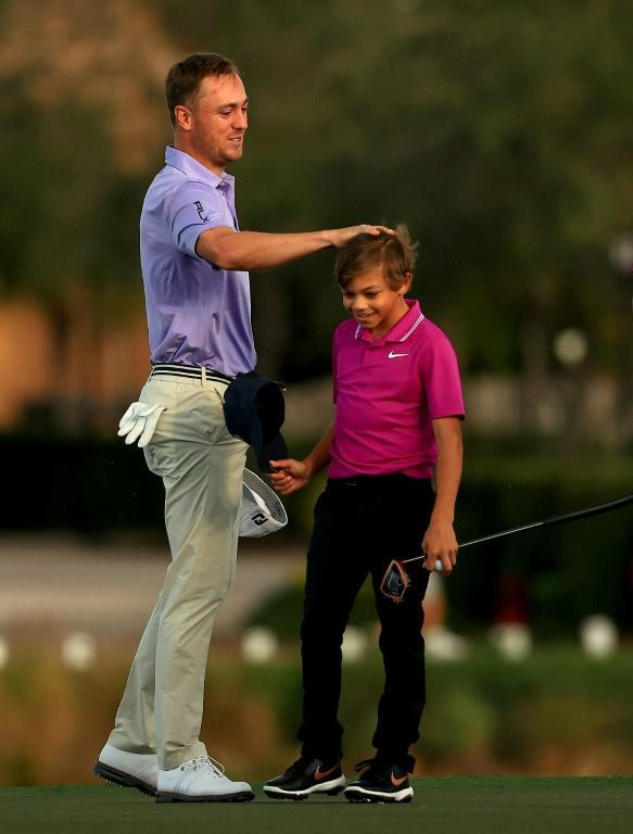 Justin Thomas congratulates Charlie Woods on the 18th green in the first round of the PNC Championship in Orlando, Florida