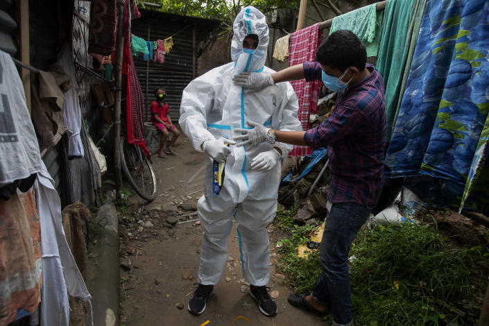 A heath worker helps another to wear protective suit before collecting swab samples of people to test for COVID-19 in Gauhati, Assam, India, Monday, May 17, 2021. (AP Photo/Anupam Nath)
