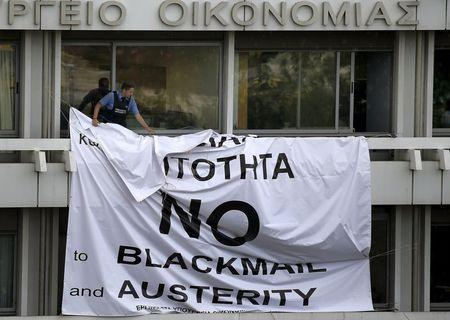 A security guard removes a banner placed earlier by protesters from a balcony of the Finance Ministry in Athens, Greece, July 1, 2015. REUTERS/Yannis Behrakis