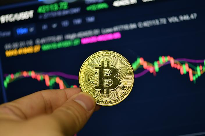 CHINA - 2021/05/20: In this photo illustration a Bitcoin is seen on display with a Bitcoin price trend chart in the background. (Photo Illustration by Sheldon Cooper/SOPA Images/LightRocket via Getty Images)