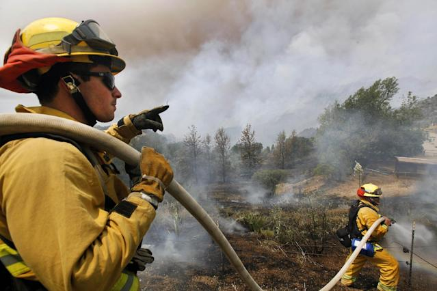 Firefighters from Riverside, Calif. work to extinguish a brush fire at Point Mugu, Calif., Friday, May 3, 2013. A Southern California wildfire carving a path to the sea grew to more than 15 square miles and crews prepared Friday for another bad day of gusting winds and searing weather. (AP Photo/Nick Ut)