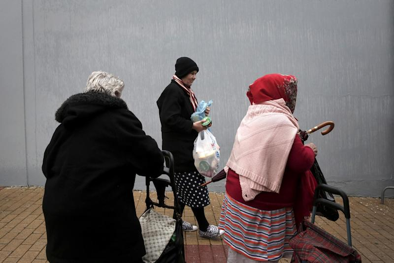 Women hold bags with donated food as they leave a New Year's meal for the homeless organized by the municipality of Athens, Wednesday, Jan. 1, 2014. Homelessness has increased dramatically during the financial crisis in Greece, which has depended on international rescue loans for more than three years. (AP Photo/Petros Giannakouris)