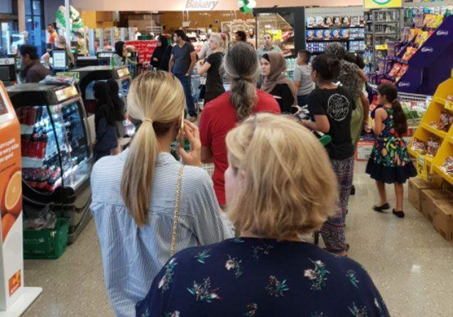 Shoppers line up at a Woolworths store in Sydney following the IT issue. Source: Twitter/ Nazli Aktac