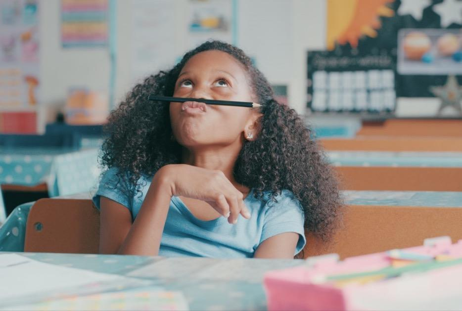 Young girl looking bored while playing at a school desk.