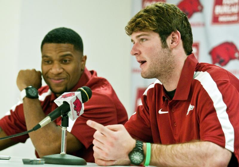 FILE - In this Jan. 21, 2012 file photo, Arkansas quarterback Tyler Wilson, right, and running back Knile Davis, left, speak to the media about foregoing the draft to return to college football, during a news conference in Fayetteville, Ark. (AP Photo/April L. Brown, File)