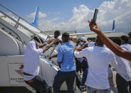 Haitians deported from the United States try to board the same plane in which they were deported, in an attempt to return to the United States, on the tarmac of the Toussaint Louverture airport in Port-au-Prince, Haiti Tuesday, Sept. 21, 2021. (AP Photo/Joseph Odelyn)