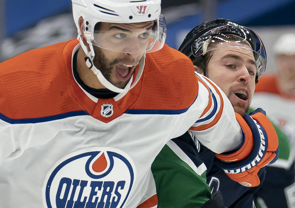 Edmonton Oilers defenseman Darnell Nurse (25) fights for control of the puck with Vancouver Canucks left wing Tanner Pearson during the first period of an NHL hockey game Thursday, Feb. 25, 2021, in Vancouver, British Columbia. (Jonathan Hayward/The Canadian Press via AP)