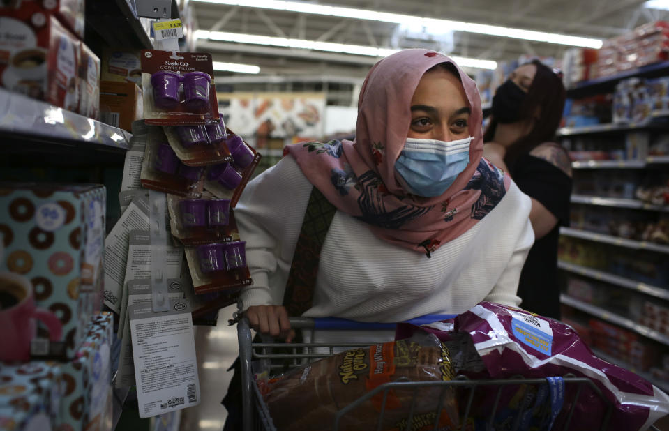 Amirah Ahmed, 17, pushes a cart while shopping with her family at a Walmart in Fredericksburg, Va., on Saturday, Aug. 14, 2021. (AP Photo/Jessie Wardarski)
