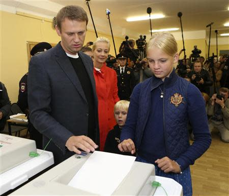Russian opposition leader Alexei Navalny (L), accompanied by his wife Yulia (2nd L) and children Dasha and Zakhar (2nd L), casts his vote at a polling station in Moscow September 8, 2013. REUTERS/Sergei Karpukhin