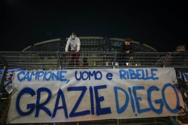 Supporters stand on fencing above a banner reading 'Champion, man, rebel, thank you Diego' placed outside the San Paolo in Naples
