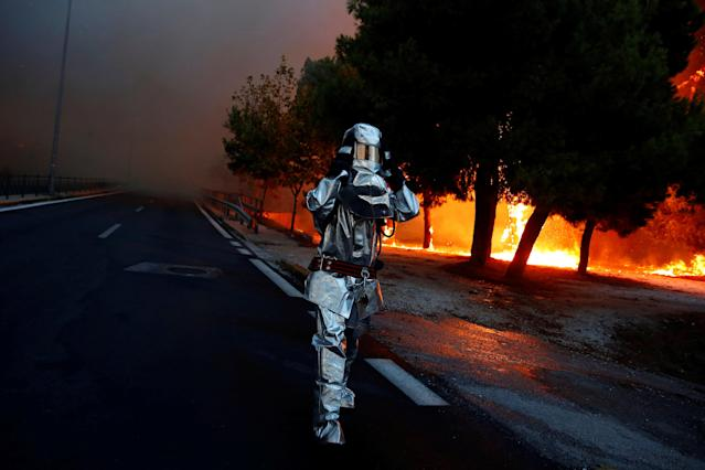<p>A firefighter wears a flame resistant uniform as wildfire burns in the town of Rafina, near Athens, Greece, July 23, 2018. (Photo: Costas Baltas/Reuters) </p>