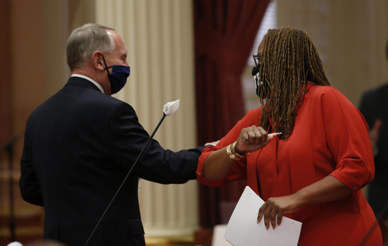 State Sen. Richard Roth, D-Riverside, and Sen. Holly Mitchell, D-Los Angeles, greet each other with an elbow bump at the Capitol, in Sacramento, Calif., Wednesday, June 24, 2020. By a 30-10 vote the Senate approved a a measure to place a proposed Constitutional amendment on the November ballot to let voters decide whether to repeal a ban on affirmative action policies in government and public colleges and universities. The amendment would allow government and public colleges and universities to consider race in their hiring, contracting and admissions decisions. Mitchell carried the bill in the Senate. (AP Photo/Rich Pedroncelli)